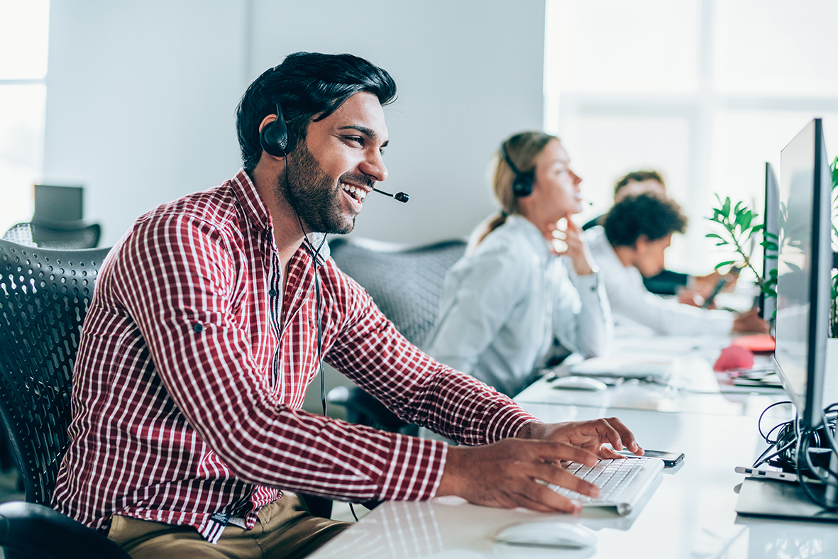 Smiling handsome ethnicity businessman working in call center. Shot of a cheerful young man working in a call center with his team. Confident male operator is working with colleagues. Call center operators sitting in a row at desks.