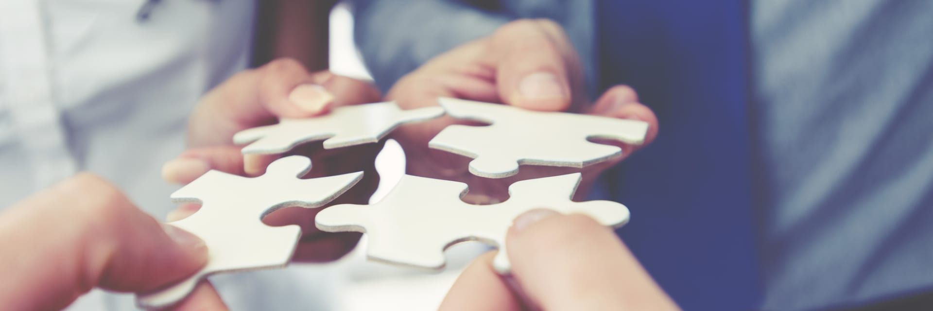 group of people holding puzzle pieces together