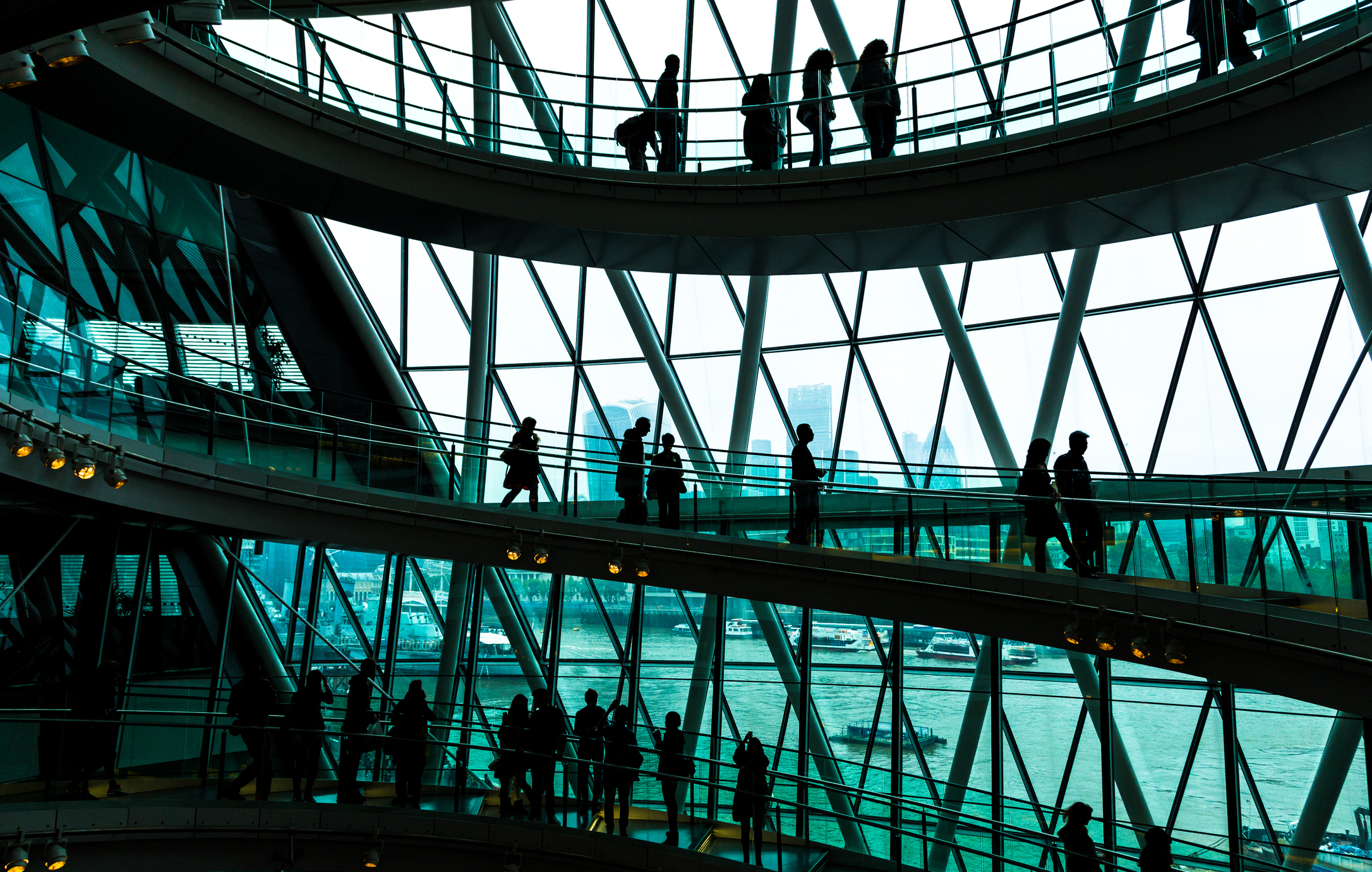 business people on a spiral staircase in a large building
