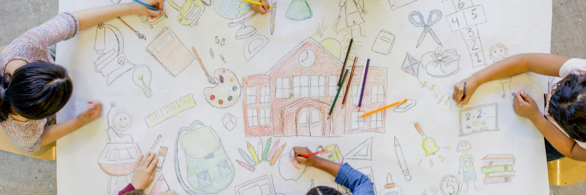 overhead view of children drawing on large piece of paper