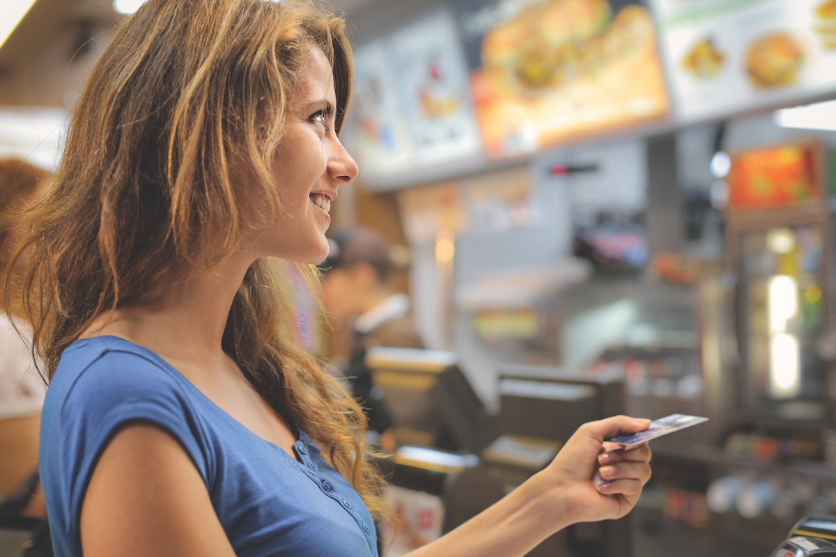Woman paying with credit card at a fast food restaurant