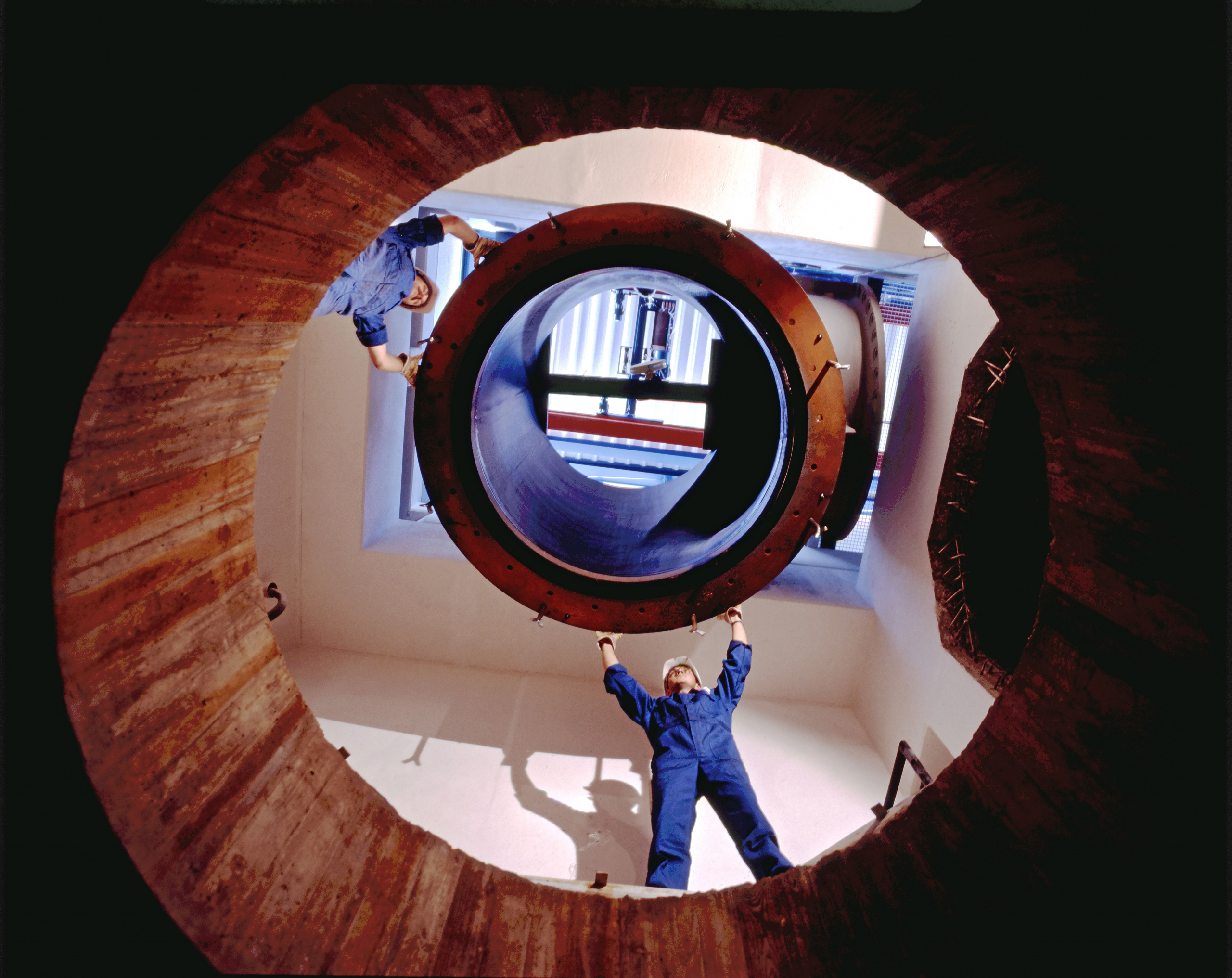 Two workers fitting together large pipe pieces