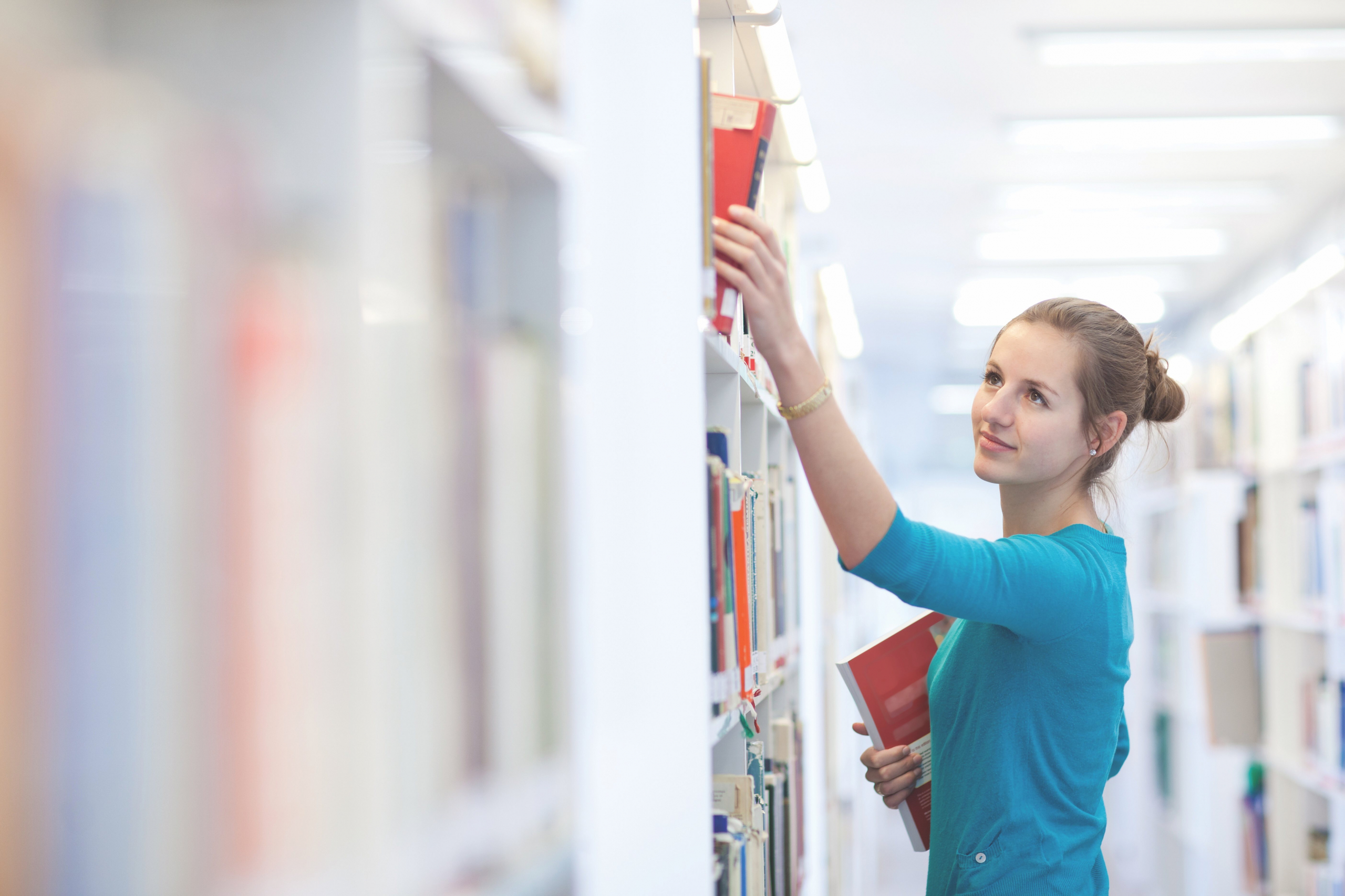 College student grabs book off of shelf in library