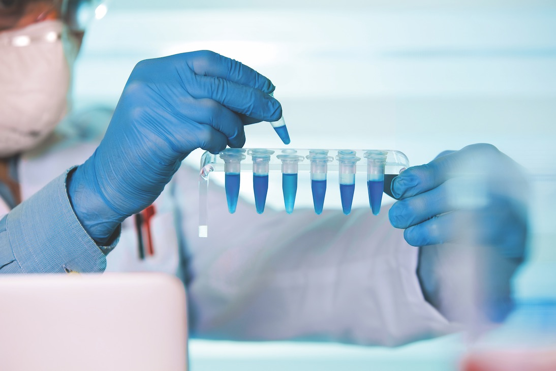 Scientist holding blue samples in test tubes in a lab
