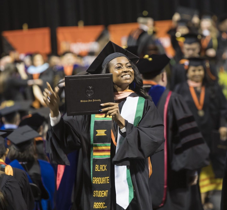 OSU student holding diploma at graduation