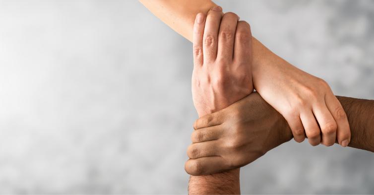 three hands interlocked to represent partnership