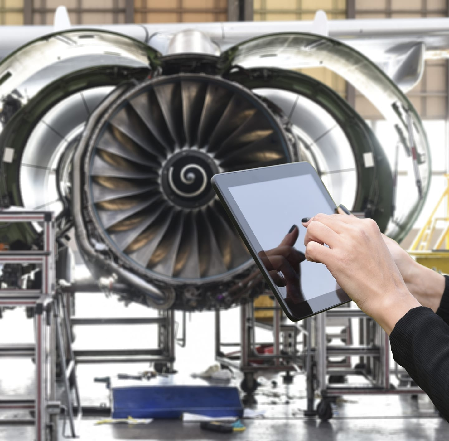 woman holding tablet in front of airplane engine