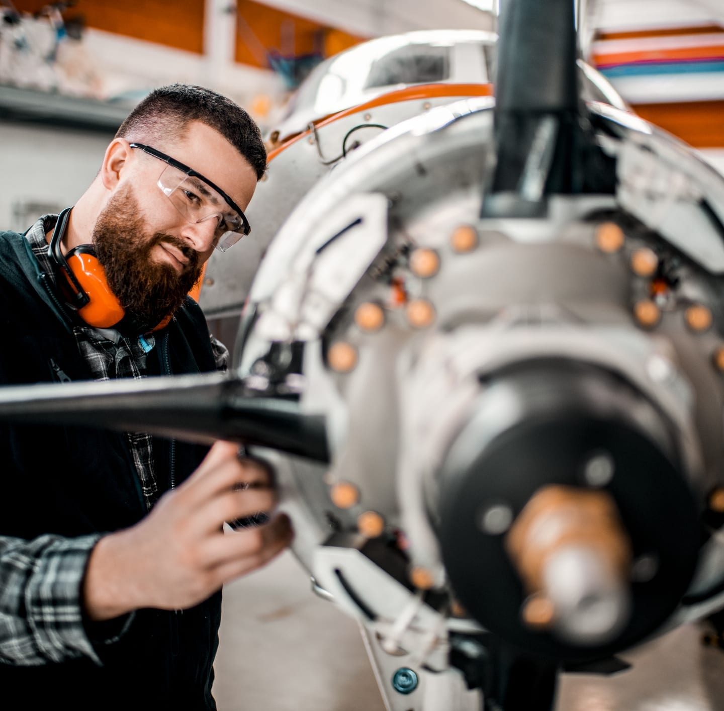 man with ear protection assembling aircraft engine